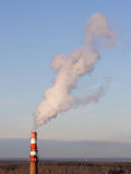 Smoking chimney. Stand-alone red-white boiler-house chimney smoking Stock Photography