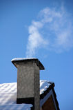 Smoking Chimney. Chimney of an Alpine Cottage smokes from the fire below Royalty Free Stock Image