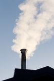 Smoking Chimney. Smoke billows from a rooftop chimney stock photo