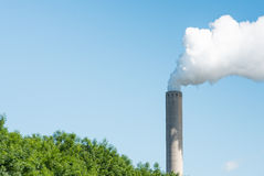 Smoking chimney against a bright blue sky Stock Photography
