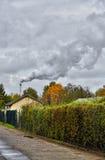 Smoking chimney behind garden plots Royalty Free Stock Photography