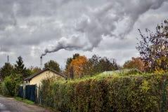 Smoking chimney behind garden plots Royalty Free Stock Photo