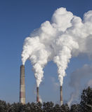 Smoking chimney of industrial buildings complex. Stock Photos