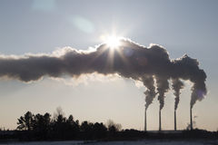 Smoking chimney of industrial buildings complex. high pollution from coal power plant. Smoke against the sun. Stock Photos