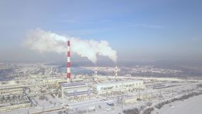 Smoking chimney on industrial plant aerial landscape. Drone view smokestacks on industrial area at heating plant. Boiler. Pipe and smoke in winter city stock footage