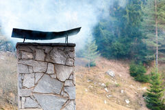 Smoking chimney in mountain. Large smoking chimney made of stone bricks with several pine trees in background Stock Image