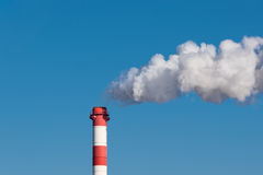A smoking chimney of a plastic manufacturing factory Stock Photo