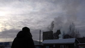 A smoking chimney on the roof of a house in front of the evening sky.  stock video