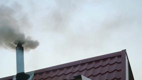 Smoking chimney on the roof of a house in front of the evening sky in slowmotion. 1920x1080 stock footage