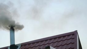 Smoking chimney on the roof of a house in front of the evening sky in slowmotion. 1920x1080 stock video footage