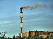 Smoking chimney smelter. Smoking chimney smelter against the blue sky Royalty Free Stock Photo