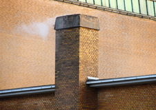 Smoking Chimney on Yellow Brick Tile Building Royalty Free Stock Photos