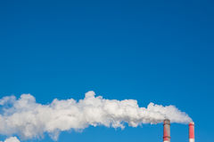Smoking chimneys against the blue sky Stock Photo