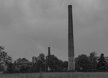 Smoking chimneys in black and white tone. Old smoking chimneys of an abandoned factory royalty free stock photo