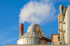 Smoking chimneys of a factory against a blue sky Royalty Free Stock Images