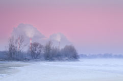 Smoking chimneys over a misty and freezing river during dusk Stock Image