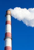 Smoking chimneys. Picture tubes for heat power plant with clouds of smoke on a blue background Royalty Free Stock Photo