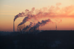 Smoking chimneys at sunrise. Stock Images