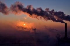 Smoking chimneys at sunrise Royalty Free Stock Images