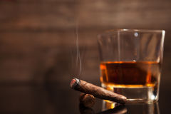 Smoking cigar and glass of whiskey in the background Royalty Free Stock Photography