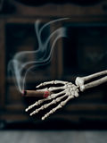 Smoking Cigar. In skeleton hand - representative of the hazard of smoking to health Stock Images