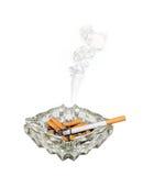 Smoking cigarette in ashtray. A cigarette or fag burns shorter in a glass ashtray Stock Image