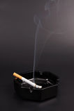 Smoking cigarette in an ashtray Stock Photo