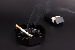 Smoking cigarette in an ashtray Stock Photography