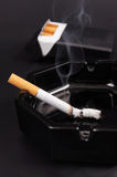Smoking cigarette in an ashtray Stock Image