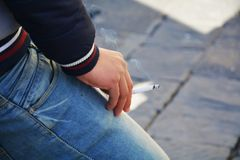 Smoking a cigarette in a bored posture Stock Images