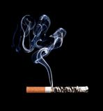 Smoking cigarette. Isolated on black. Royalty Free Stock Photos
