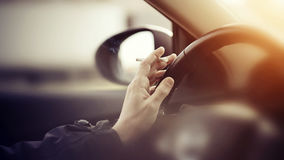 Smoking cigarettes while driving. Smoking cigarettes at the wheel while driving a car Royalty Free Stock Photo