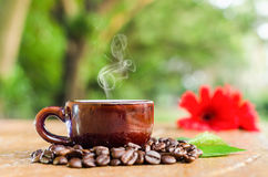 Smoking Coffee in a mug. Coffee in a mug & beans with flower and leaves Stock Images