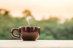 Smoking Coffee in a mug. Coffee mug or tea cup with smoke in natural otutdoor Stock Image
