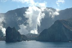 The smoking crater of a volcano seen from the sea. Smoke and steam is rising from the crater of an active volcano. The volcano is an island, and water is in the Royalty Free Stock Photography