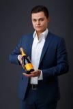 Smoking d'uso del signore che tiene una bottiglia del champagne immagine stock