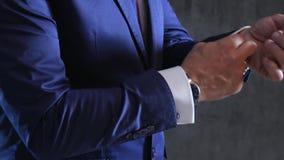 Smoking di lusso blu del maschio che corregge il polsino, l'anello di oro e l'orologio sulle armi contro la parete grigia archivi video