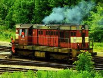 Smoking diesel train traveling on the freight station Stock Photo