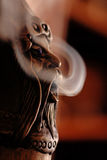 Smoking doll. Closeup view of a smoking incense doll with smoke Royalty Free Stock Photography