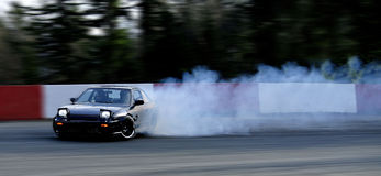 Smoking Drift Car. Car burning rubber drifting a corner Stock Image