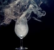 Smoking drink. Detail of a glass and smoke stock images