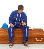 Smoking, drinking beer man sits on coffin Royalty Free Stock Photography