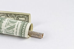 Smoking is the emission of money. Cigarette wrapped in a 1 dollar bill Stock Image