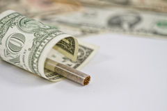 Smoking is the emission of money. Cigarette wrapped in a 1 dollar bill Royalty Free Stock Photography