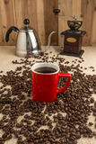 Smoking Espresso in red cup with coffee beans and old coffee mil Stock Image