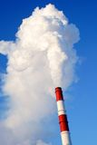 Smoking factory chimney. Clouds of smoke rising from industrial chimney with blue sky background Royalty Free Stock Photography