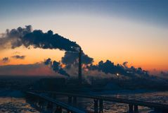 Smoking factory at sunset Royalty Free Stock Images