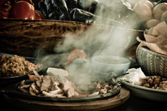 Smoking Fajitas - Mexican Food. Fajitas on a skillet with fresh fruit and vegetables in background Stock Photo