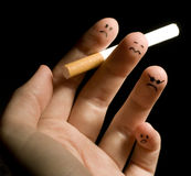 Smoking fingers. Fingers holding cigarette. Sad smiley painted on fingertips. Conception of addiction and anti-smoking royalty free stock images