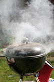 Smoking grill outdoors. A black grill emitting clouds of smoke Stock Images
